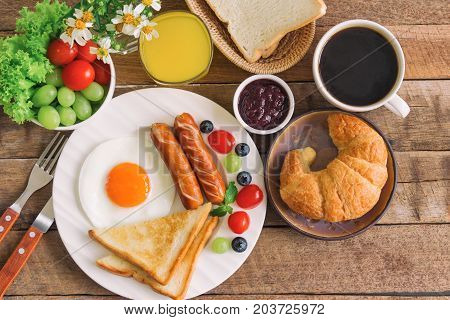 Homemade breakfast with sunny side up fried egg toast sausage fruits vegetable croissant strawberry jam black coffee and orange juice in top view flat lay concept. Delicious homemade american breakfast. American breakfast for family.