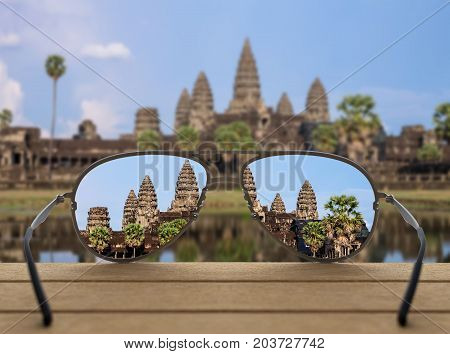 Conceptual image of Angkor Wat focused in glasses lenses over the photo blurred of Angkor Wat at Siem Reap. Cambodia