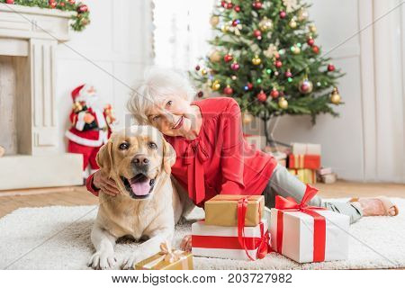 Soulmate. Portrait of cheerful senior lady is looking at camera with smile while lying on white carpet with lovely dog among Christmas presents. Decorated tree with Santa Claus are on background