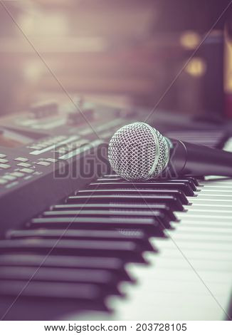 microphone on music keyboard with music brand blurred background music instrument concept