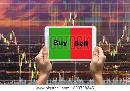 female hands holding a tablet touch screen showing buy and sell over the Stock market exchange information and Trading graph on the cityscape at night backgroundBusiness trading concept, 3D illustration