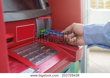 Closeup of male hands using and with insert ATM card into bank machine for withdraw the money business technology banking concept