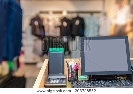 Cashier operating at the cash desk over the Abstract blurred photo of clothing store in a shopping mall business and shopping concept