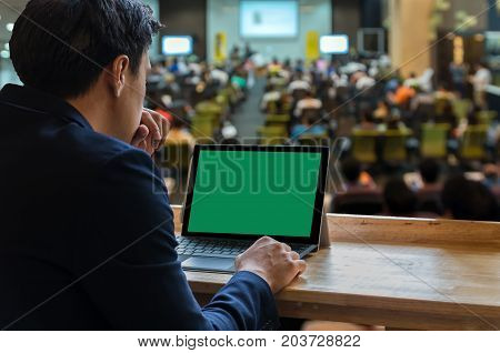 Businessman sitting and using computer laptop showing the blank green screen over the Meeting Blurred background at bright conference hall Business meeting concept