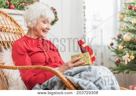 Christmas miracle. Cheerful senior lady is sitting in rocking chair and opening gift box while expressing surprise and happiness. Copy space in the right side