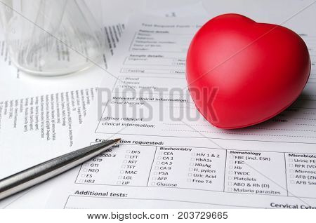red heart pen test tube beaker and patient information form on desk heart healthcare technology medical diagnosis heart disease medical report record and history patient concept