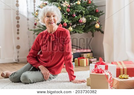Christmas mood. Portrait of charming senior lady is sitting on floor among presents and expressing happiness. She is looking at camera with joy. Copy space in the right side