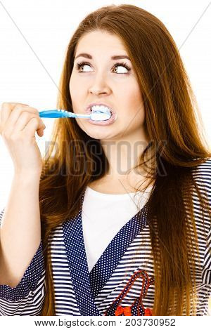 Woman wearing dressing gown brushing cleaning teeth. Funny girl with toothbrush. Oral hygiene. Isolated on white