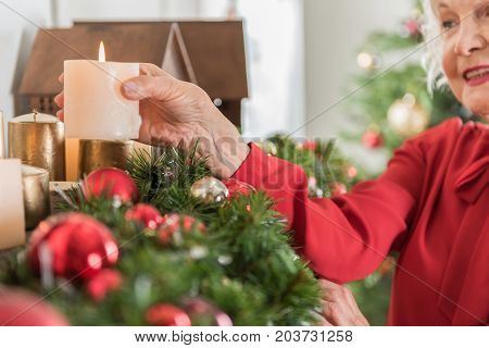 All is merry and bright. Close-up of hand with candle of senior lady who is decorating her house while expressing gladness