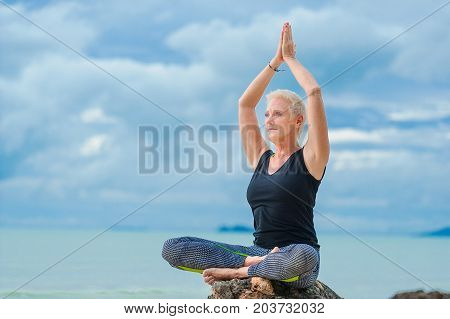 Beautiful Mature Aged Woman Doing Yoga On A Desert Tropical Beach
