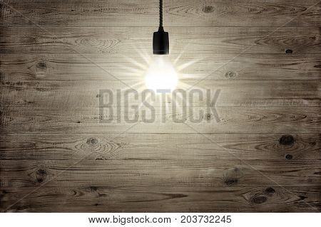 Lightbulb shining over brown wood texture background