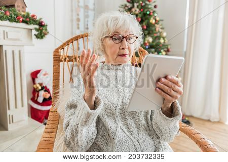How to use. Senior woman is holding tablet and looking at screen while expressing discontent and perplexity. Christmas tree and Santa Claus are on background