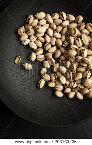 Bowl with pistachios on a black table background