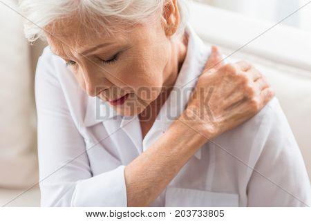 Unpleasant feeling. Old cheerless gray-haired woman is touching her neck with closed eyes while expressing strong pain
