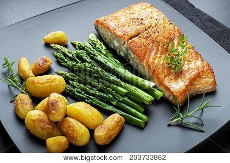 Roasted salmon fillet with asparagus and potatoes on black background