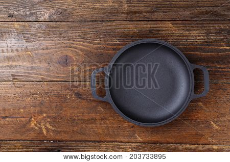 Portioned cast-iron frying pan on a wooden background space for text
