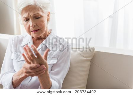 Arm ache. Gray-haired mature woman is suffering from arthritis. She is looking at her hand and feeling awful pain. Copy space in the right side