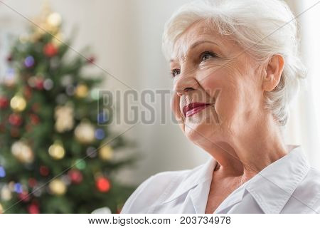 Remembering something. Close-up of face of elderly woman is looking aside thoughtfully while sitting with Christmas tree on background. Copy space in the left side