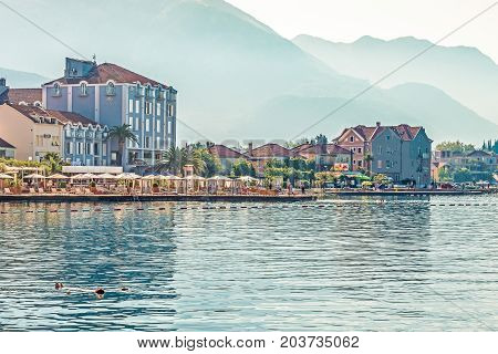 TIVAT, MONTENEGRO - August 24, 2017: View of the beautiful beach in Tivat on the shore of Kotor Bay. Tivat is a famous resort in Montenegro.