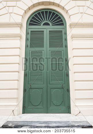 Large green wooden door in fron of the European style building.
