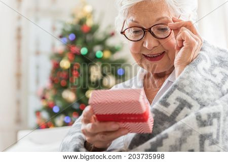 Christmas time. Joyful senior lady is sitting with gift box in her hand and reading congratulation with smile. She is touching her glasses while expressing curiosity. Copy space in the left side