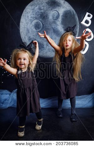 Two Cute Little Sisters Are Dressed In Witch Costumes