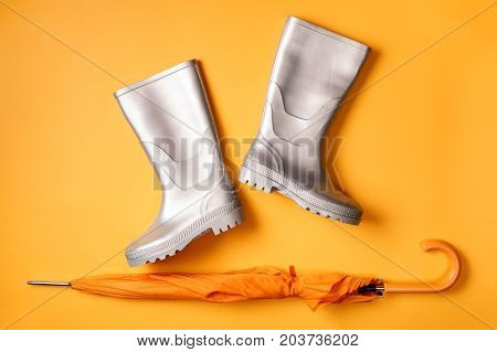 From above shot of stylish silver gumboots and umbrella on orange background.