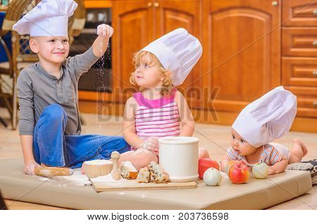 Boy, girl and a newborn kid with them in chef's hats sitting on the kitchen floor soiled with flour playing with food making mess and having fun