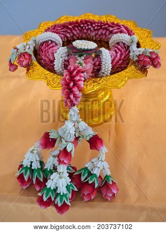Lei of flowers garland on tray with pedestal for worship
