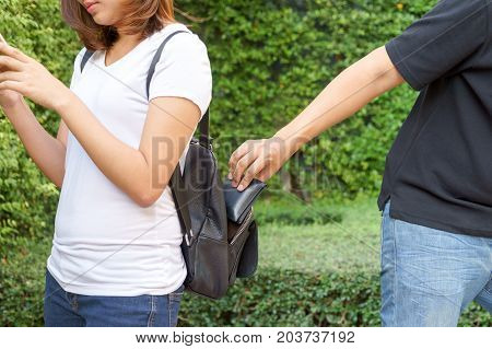 Thief trying to steal the wallet in the backpack and walk away while woman using mobile phone in the park