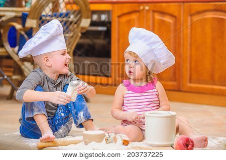 Two Kids In Chef's Hats Sitting On The Kitchen Floor Soiled With Flour, Playing With Food, Making Me