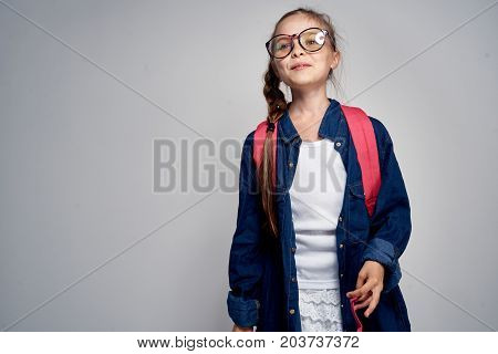 little girl in sunglasses, with a backpack, in a denim shirt.