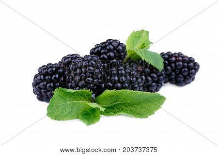 A picture of a heap of ripe, juicy, natural blackberries, isolated on a white background. A pile of healthful and organic berries with fresh leaves of mint. Raw saturated black berries.