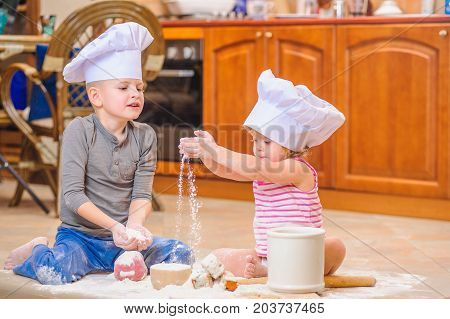 A boy and a girl in chef's hats sitting on the kitchen floor soiled with flour playing with food making mess and having fun