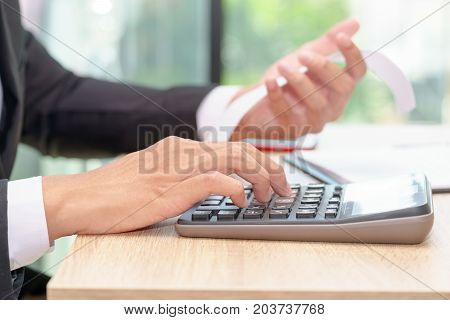 Hands of businessman pushing calculator for calculating a receipt - financial concept