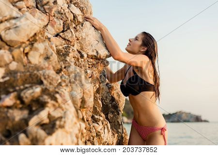 Young female free climber in bikini on a cliff at sunset.
