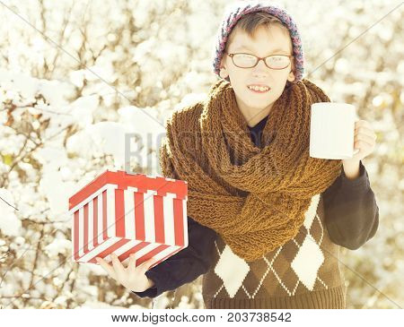 small smiling boy or cute nerd kid in glasses hat sweater and fashionable knitted scarf holds red christmas or new year gift box and cup in sunny winter outdoor on natural background