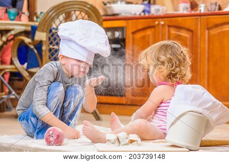 Two siblings - boy and girl - in chef's hats sitting on the kitchen floor soiled with flour playing with food making mess and having fun