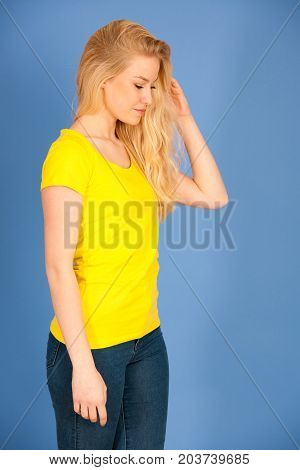 Beautiful Blonde Teenage Girl In Yellow T Shirt And Jeans Over Ble Background