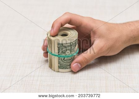 A man holds a bunch of money twisted in a bunch and tied with a green rubber band on a light textured background