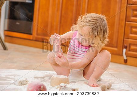 Cute little girl sitting on the kitchen floor soiled with flour playing with food making mess