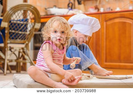 Two siblings - boy and girl - in chef's hats sitting on the kitchen floor soiled with flour, playing with food, making mess and having fun