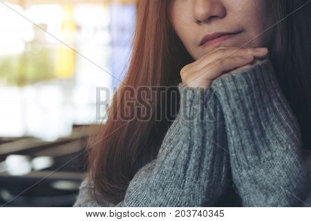 Closeup portrait image of a lonely beautiful Asian woman sitting with chin resting on her hands alone in modern cafe