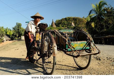 MRAUK-U MYANMAR - 25 JANUARY 2011: The driver of the rickshaw is pumping the wheel up on a dirt road in Burma