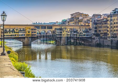 bank of arno river crossed by ponte vecchio in hours near the sunset