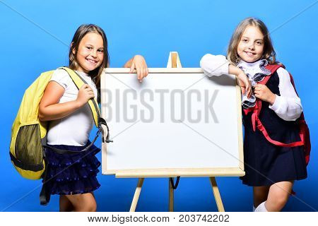 Schoolgirls Next To Marker Board On Blue Background