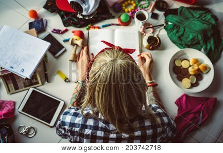 top view of young blonde woman in a bandana read a book lying on the floor. The mess in the room. Modern student.