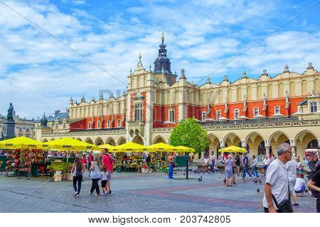 Krakow/Poland- August 15, 2017: view of main Market Square with walking tourists, souvenirs and flowers sellers, old Cloth Hall building, sunny summer day, blue sky
