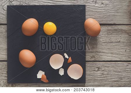 Fresh chicken brown home eggs top view with cracked eggshell and yolk on rustic slate black plate on wood background. Natural healthy food and organic cooking ingredients