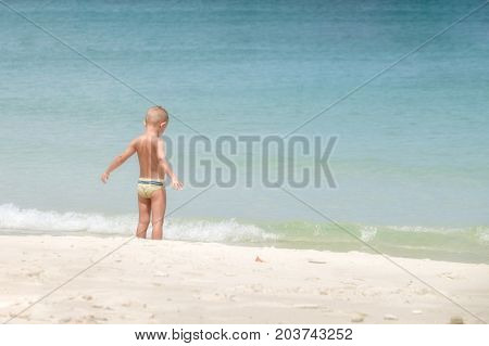 European boy age 3-5 years old stands on the beach Opening arm.